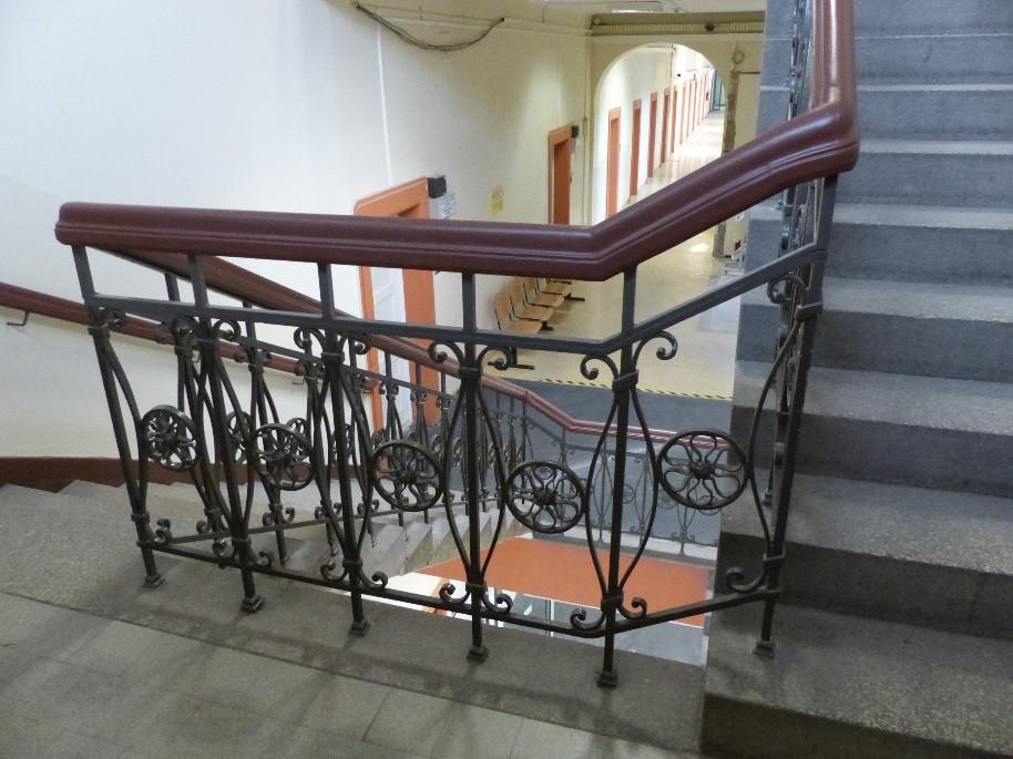 Auf dem Bild sieht man ein Treppenhaus mit einem schmiedeeisernen Geländer mit dunkelbraunerm Handlauf.