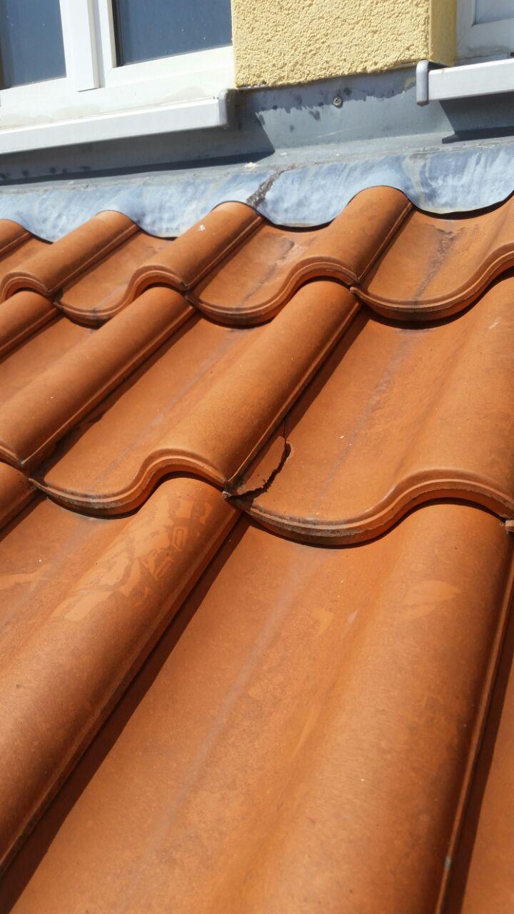 Zu sehen sind rote Dachziegel, von denen Einzelne beschädigt sind.