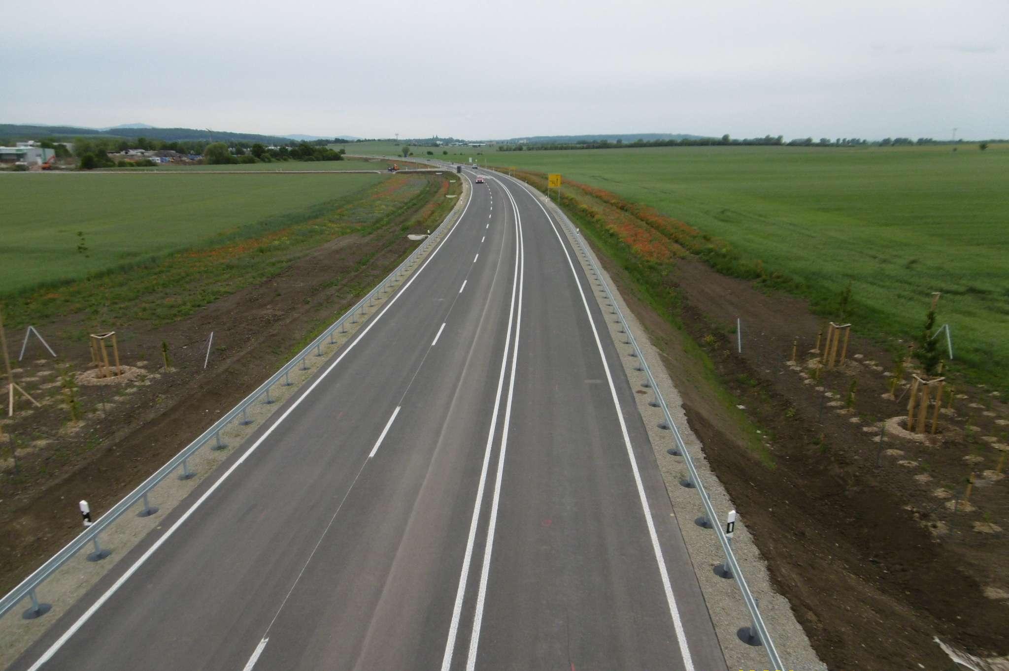 Abgebildet ist eine dreispurige Straße. Links und rechts sind Wiesen und Erde.