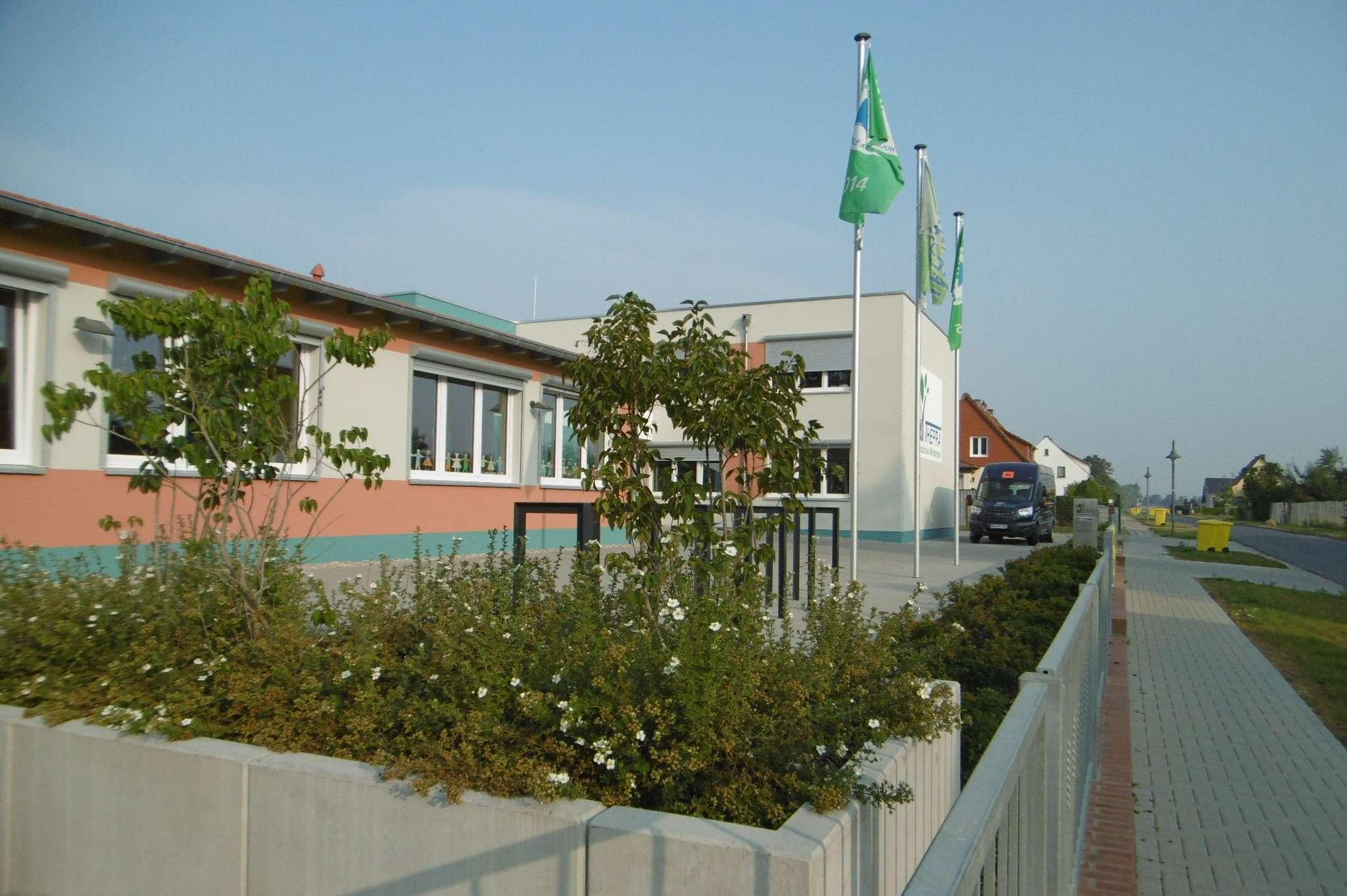 Zu sehen ist ein grauer Flachbau. Im Vordergrund ist viel Grün. Vor dem Schulgebäude wehen grüne Fahnen.