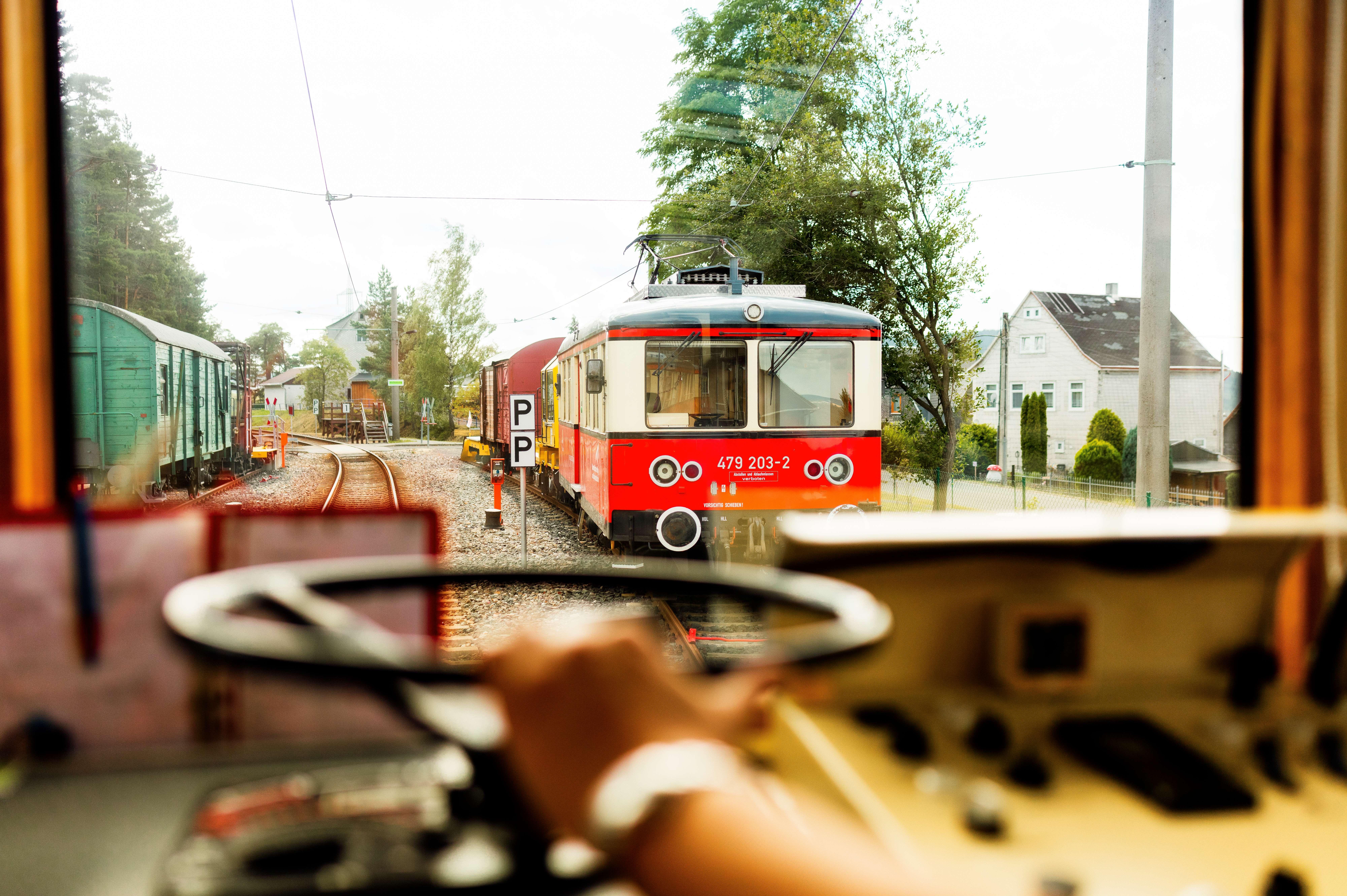 Es ist ein beigeroter Triebwagen durch ein Fenster zu sehen. Im Vordergrund sind Bedienelemente eines alten Triebwagens.
